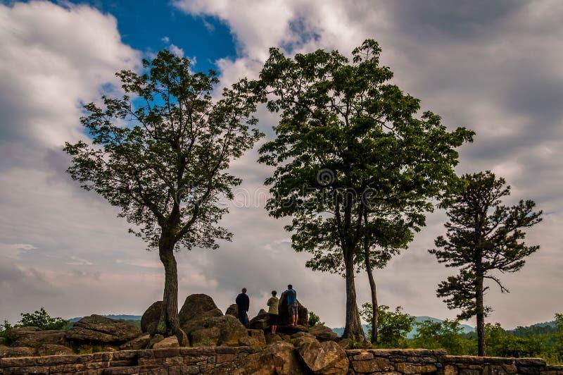 As rochas, as árvores, e os turistas em uma negligência na skyline conduzem em Sh fotografia de stock royalty free