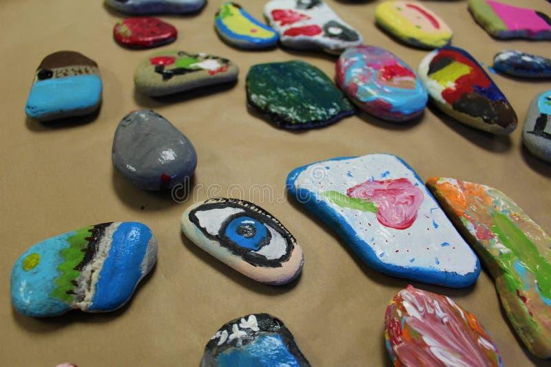 As rochas brilhantemente pintadas por crianças para uma arte da classe projetam-se na toalha de papel marrom foto de stock royalty free