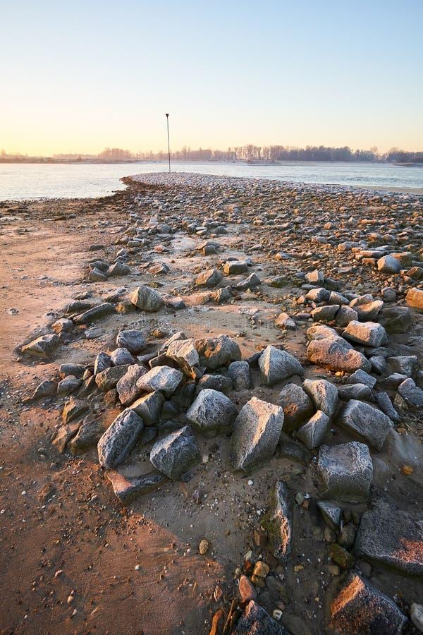 As rochas congeladas na cama de rio na manhã iluminam-se fotografia de stock royalty free