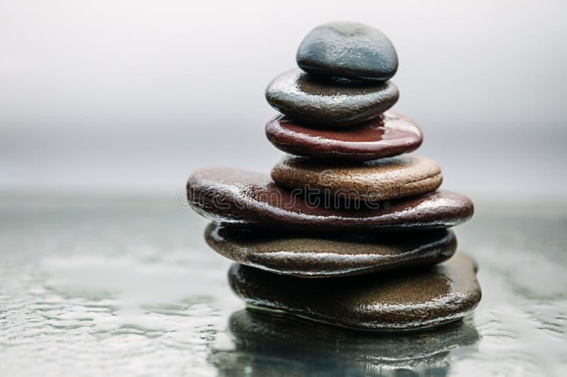 As rochas escuras ou pretas na água, fundo para termas, relaxam ou terapia do bem-estar imagens de stock royalty free