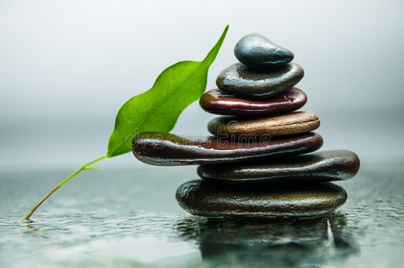 As rochas escuras ou pretas na água, fundo para termas, relaxam ou terapia do bem-estar foto de stock