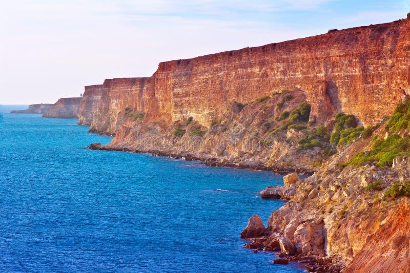 As rochas vermelhas litorais e o mar azul ajardinam a viagem do verão fotos de stock royalty free