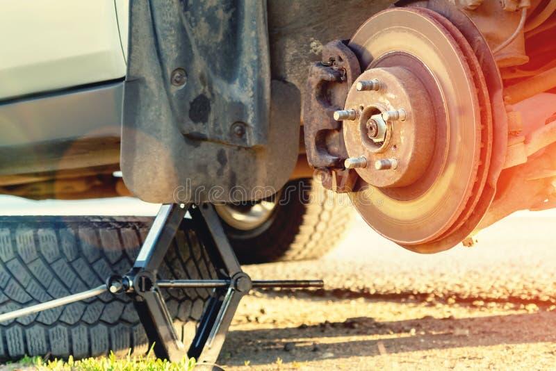 As rodas da substituição na estrada, o carro são levantadas, a roda são removidas, hão uma roda de reposição imagens de stock royalty free