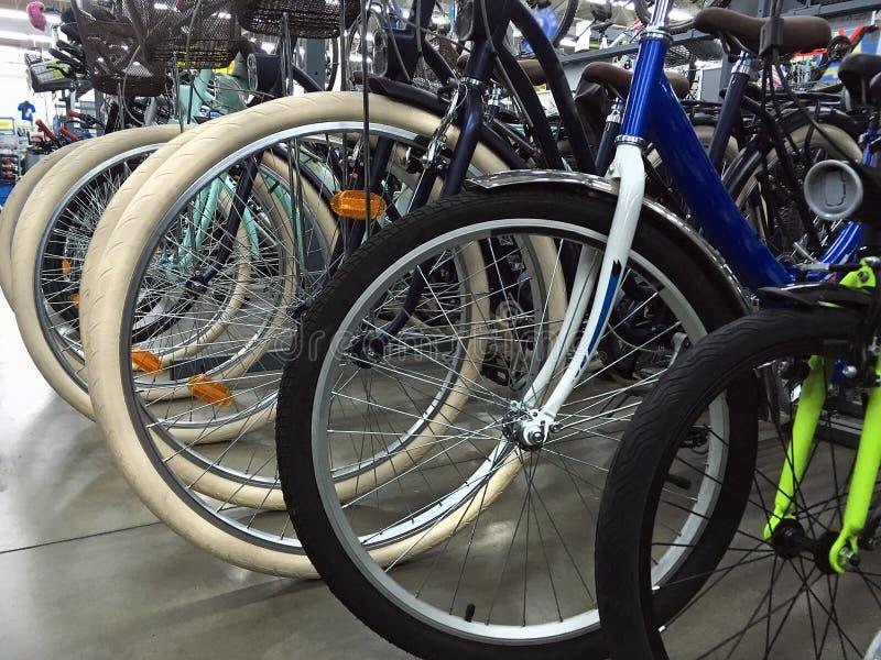 As rodas de bicicleta fecham-se acima na loja da bicicleta, em ciclos diferentes do esporte, em montanha e em bicicletas do passe fotografia de stock royalty free