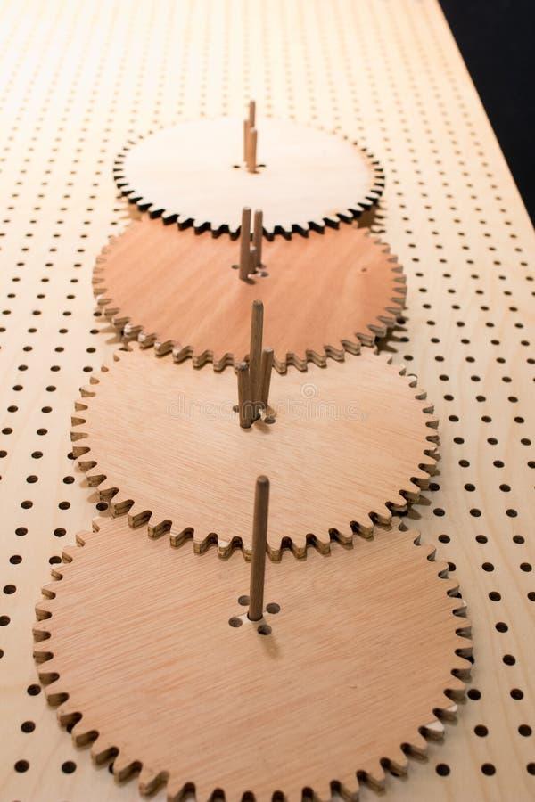 As rodas de engrenagem das engrenagens de madeira em uma tabela perfurada montaram o toge fotografia de stock royalty free