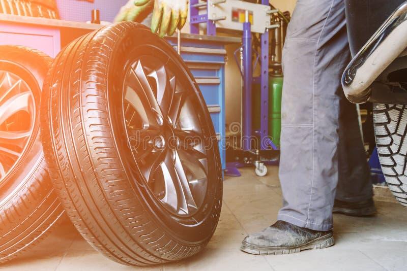 As rodas de mudanças do trabalhador do mecânico no carro na garagem do serviço de reparação de automóveis compram fotografia de stock