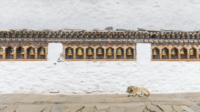 As rodas e o cão religiosos de oração em Butão imagens de stock royalty free