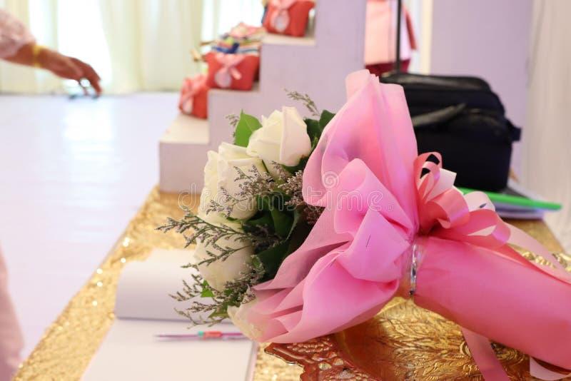 As rosas brancas envolveram com um ramalhete do fundo pastel de papel do rosa bonito imagem de stock royalty free