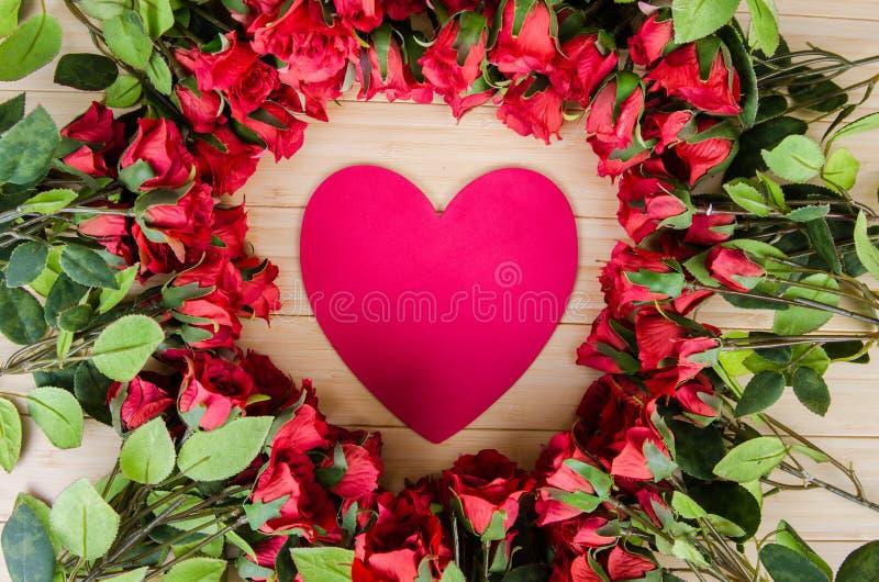 As rosas e o coração dão forma ao cartão para sua mensagem foto de stock