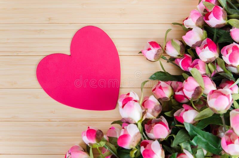 As rosas e o coração dão forma ao cartão para sua mensagem imagem de stock