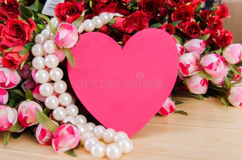 As rosas e o coração dão forma ao cartão para sua mensagem imagens de stock