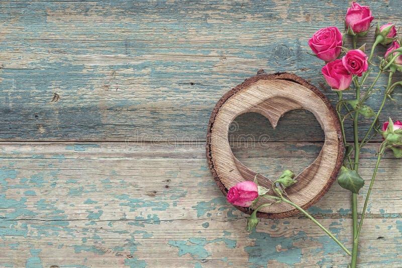 As rosas e o coração pequenos cinzelaram na madeira no grunge velho pintado imagens de stock royalty free