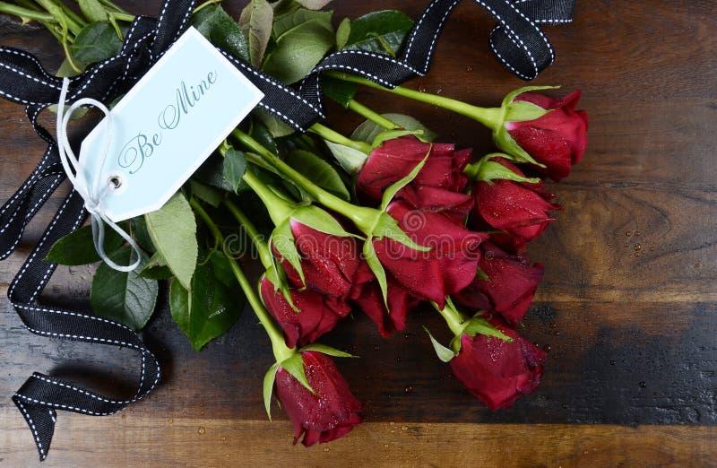 As rosas vermelhas de dia de Valentim na obscuridade reciclaram o fundo de madeira com etiqueta do presente, foto de stock royalty free