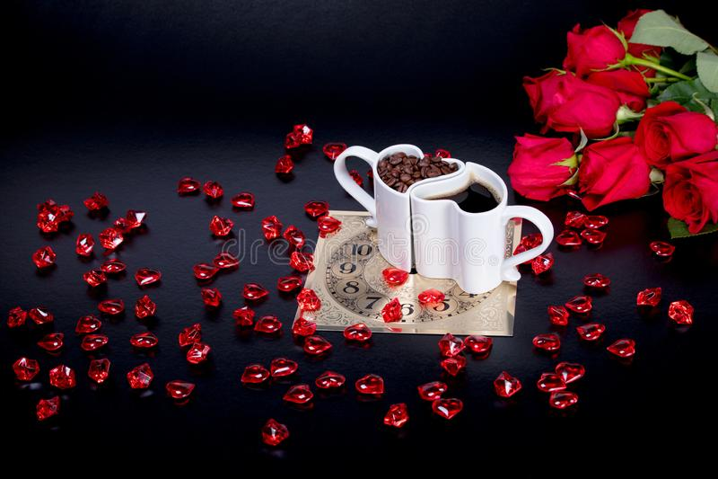 As rosas vermelhas e os corações de vidro vermelhos ao lado do coração deram forma a canecas de café foto de stock royalty free