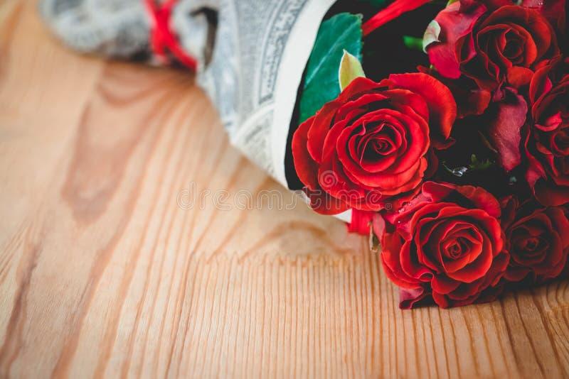 As rosas vermelhas envolveram no papel do vintage na tabela de madeira clara imagem de stock