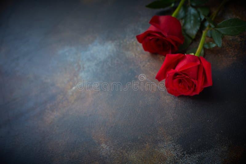 As rosas vermelhas estão sobre um fundo de mármore texturizado Um sinal de condolência, simpatia pela perda Espaço para o seu tex fotografia de stock royalty free