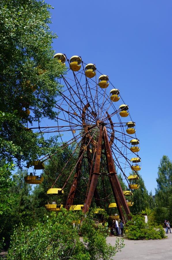 As ruínas de uma roda de ferris sentam-se em um parque de diversões abandonado em Pripyat, Ucrânia, evacuada após o desastre de C imagens de stock
