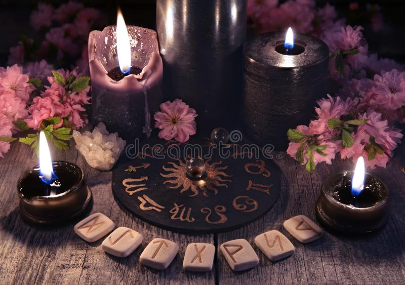 As runas, as velas pretas e o zodíaco circundam contra o fundo com as flores de sakura imagem de stock royalty free