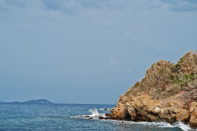 As rupturas da onda do mar em rochas da praia ajardinam As ondas do mar deixam de funcionar e espirram em rochas em Bodrum, Turqu foto de stock