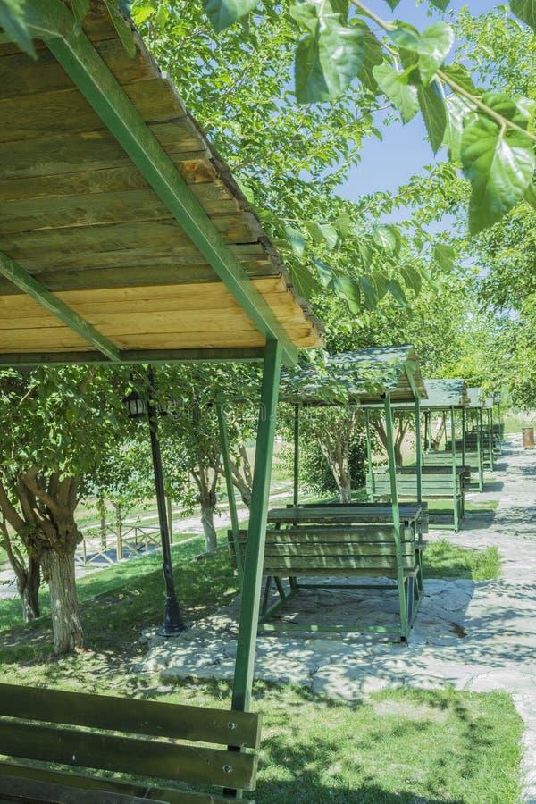 As séries de cabanas verdes do banco em um ar livre ensolarado estacionam fotografia de stock royalty free
