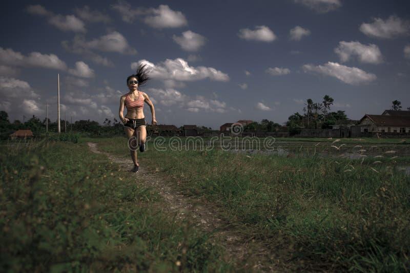 As séries running do treinamento asiático atlético da mulher do corredor malham o ar livre duro de trabalho no fundo do campo no  fotos de stock royalty free