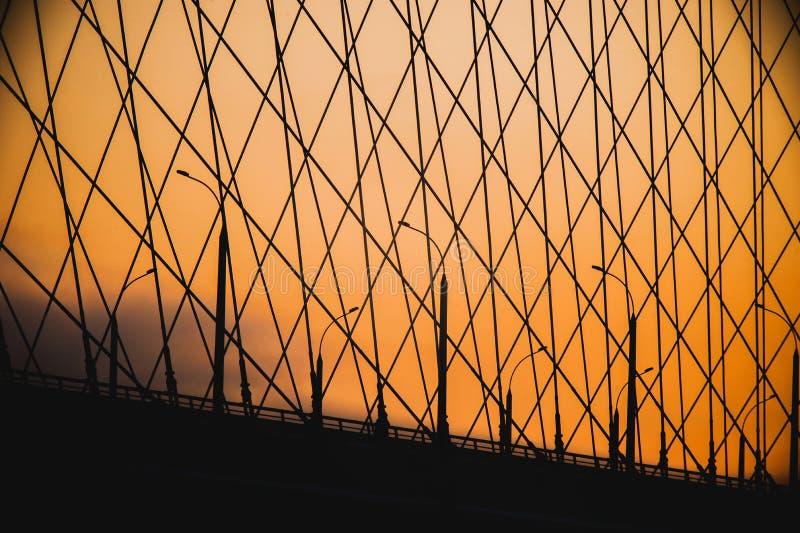 As saias constroem uma ponte sobre em lanternas da silhueta do por do sol fotos de stock