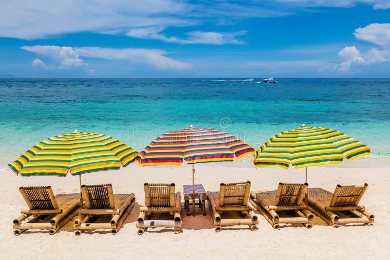 As salas de estar de Sun com os guarda-chuvas em Ilig Iligan encalham, ilha de Boracay, Filipinas imagem de stock