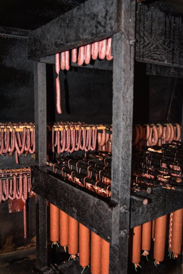 As salsichas caseiros são ficadas situadas em um fumeiro fotografia de stock royalty free
