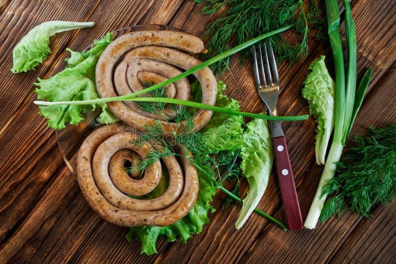 As salsichas de carne de porco grelhadas encontram-se em uma tabela de madeira com verdes: alface, aneto, salsa e cebola Vista de fotografia de stock royalty free