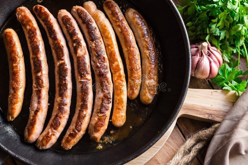 As salsichas fritadas no ferro moldaram a bandeja, crosta dourada deliciosa, alho, salsa fotografia de stock royalty free