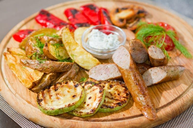 As salsichas fumado com tomates grelhados, paprika, cogumelos, abobrinha, fritaram batatas, aneto, molho ácido branco fotos de stock
