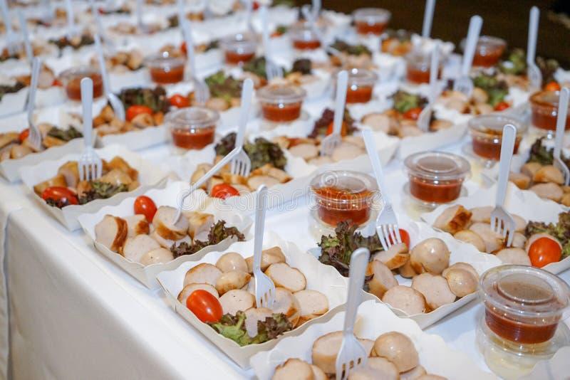 As salsichas na placa de papel com tomate, vegetal e forquilha na linha na tabela est?o prontas para servir fotografia de stock