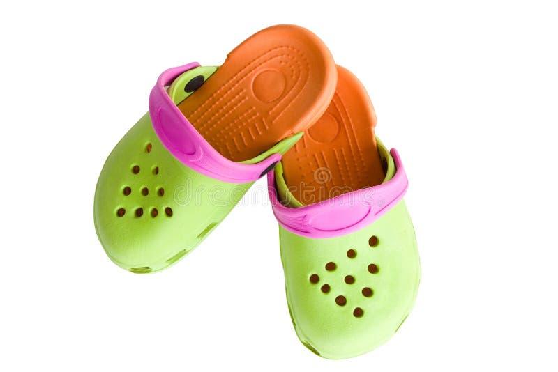 As sandálias de borracha das crianças coloridas isoladas imagens de stock