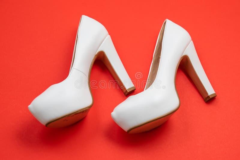 As sapatas colocadas saltos altas brancas, fundo vermelho - conceito da vista superior - colocam saltos a esquerda de passeio foto de stock
