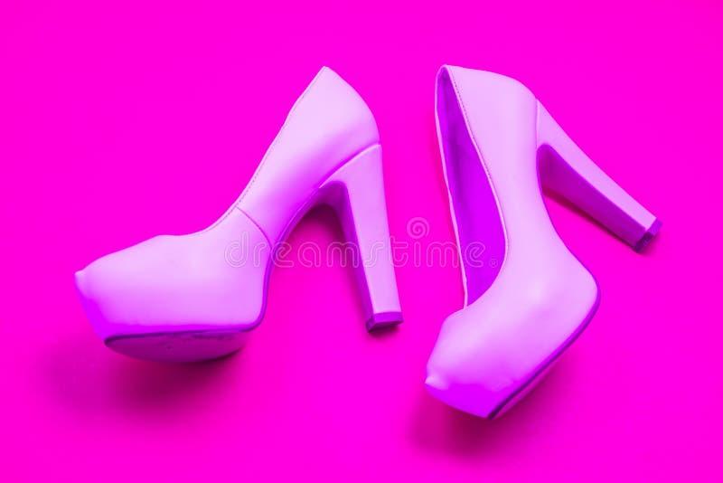 As sapatas colocadas saltos altas cor-de-rosa, fundo roxo cor-de-rosa - vista superior - colocam saltos a esquerda de passeio foto de stock