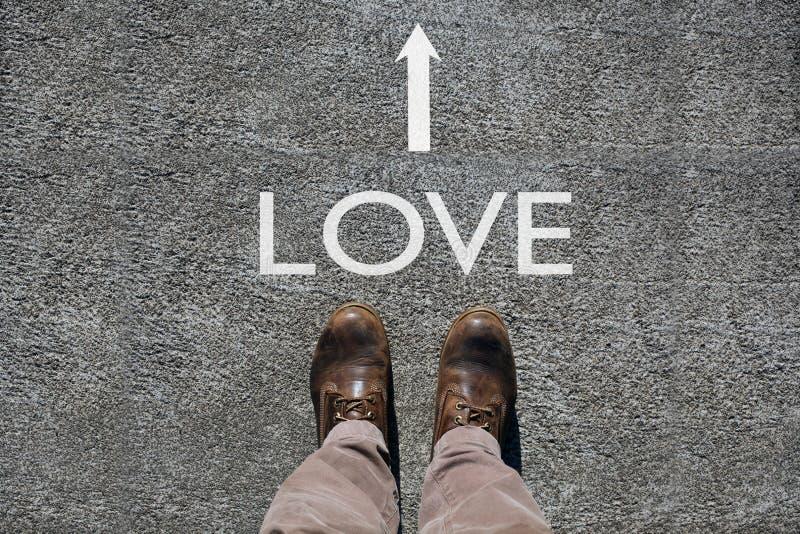 As sapatas do homem veem de cima de, amor da palavra e uma seta que indica os sentidos com o espaço da cópia para seu texto foto de stock royalty free