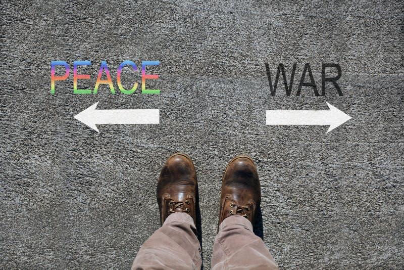 As sapatas do homem veem de cima de, paz das palavras e guerra e duas setas que indicam os sentidos com o espaço da cópia para se imagem de stock