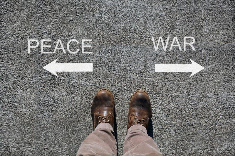 As sapatas do homem veem de cima de, paz das palavras e guerra e uma seta que indica o espaço withcopy dos sentidos para seu text fotografia de stock royalty free