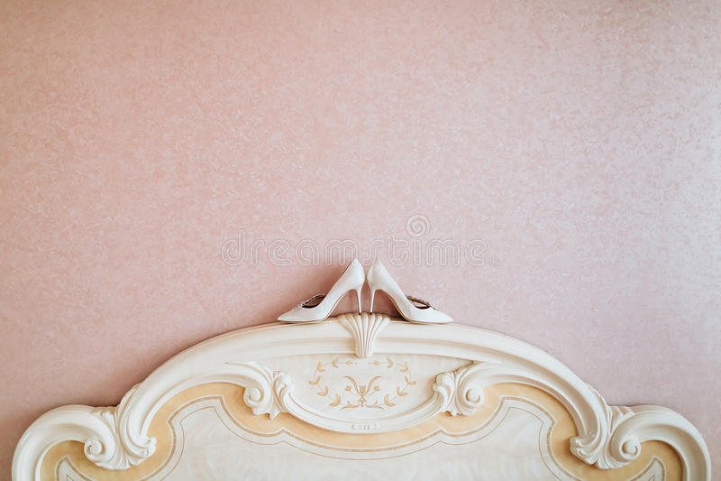 As sapatas do ` s das mulheres do casamento do marfim estão no bedhead perto da parede fotografia de stock royalty free