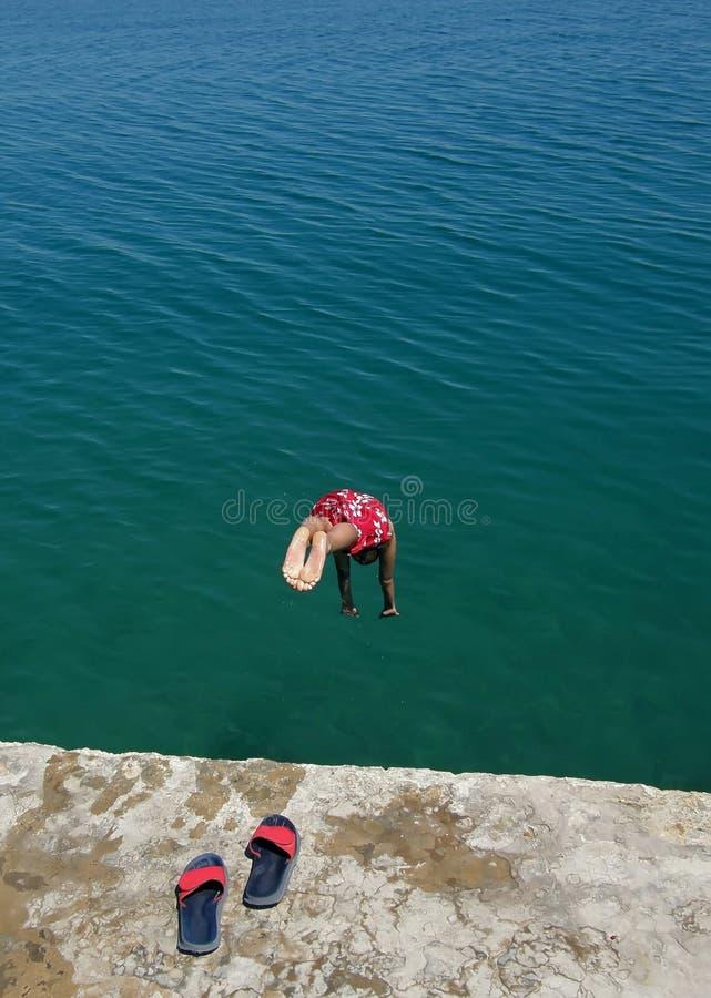 As sapatas do Slip-on, menino no porto marítimo saltam no mar fotos de stock
