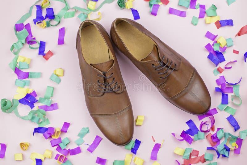 As sapatas dos homens de Brown no fundo de confetes coloridos imagem de stock royalty free