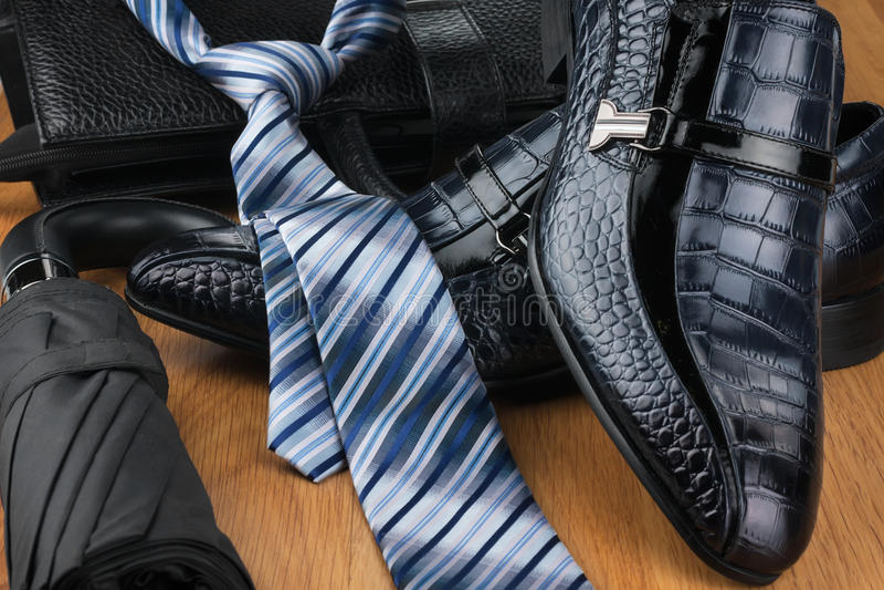 As sapatas, o laço, o guarda-chuva e o saco dos homens clássicos no assoalho de madeira fotografia de stock