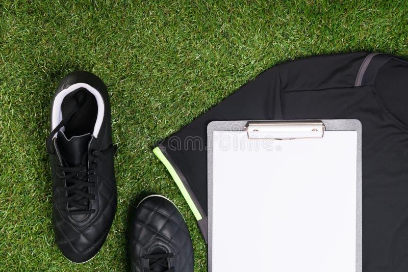 As sapatas para jogar o futebol e uma tabuleta para registros encontram-se na grama verde fotos de stock