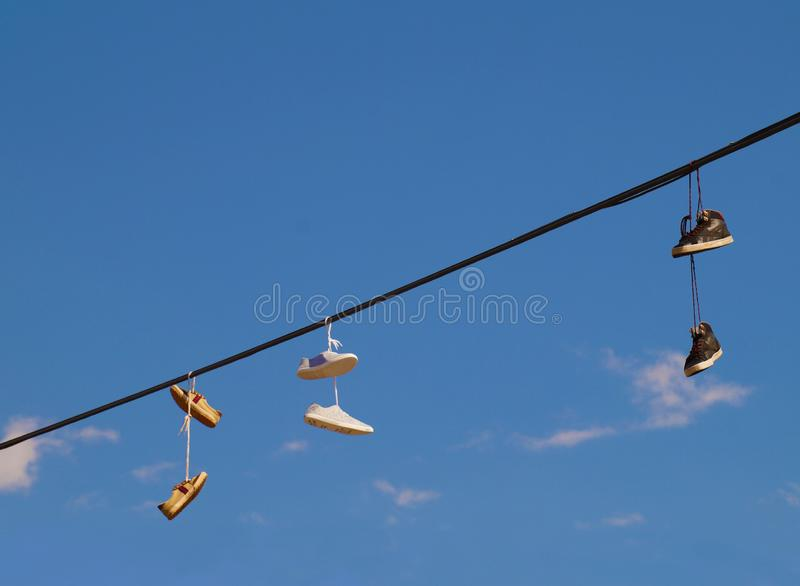 As sapatas que penduram nos fios, um formulário da lembrança sairam por turistas imagem de stock