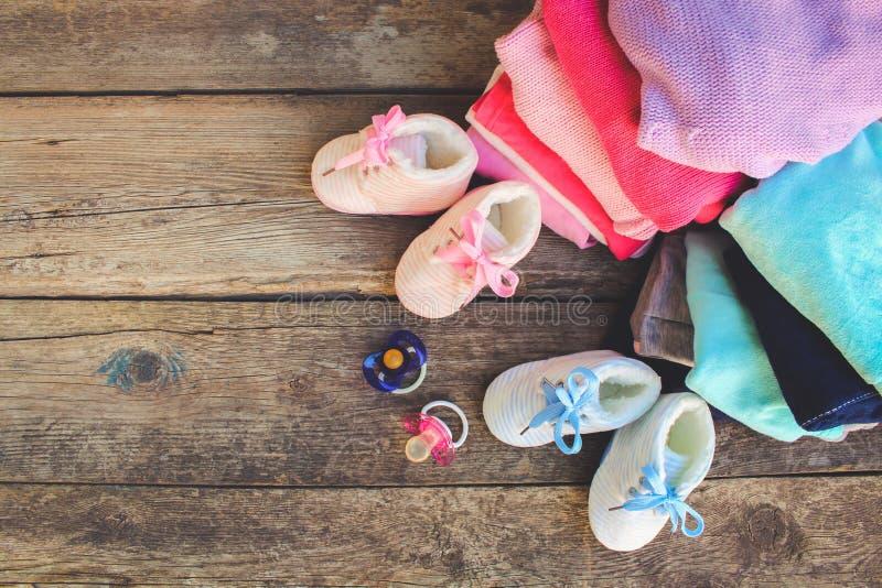 As sapatas, a roupa e as chupetas de bebê picam e azul no fundo de madeira velho foto de stock