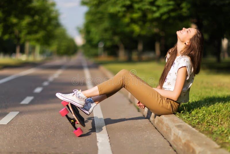 As sapatilhas bonitas t-shirt e calças do moderno da moça puseram sobre as sapatilhas e o longboard felizes skateboarding lifesty fotografia de stock royalty free