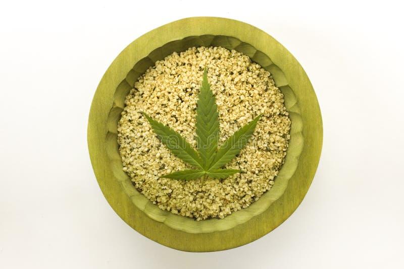as sementes de cânhamo orgânicas descascadas esverdeiam a bacia de madeira da folha do cannabis imagens de stock