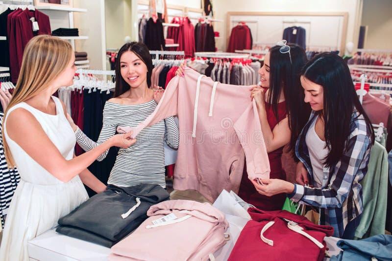 As senhoras bonitas estão na loja Estão guardando uma camiseta cor-de-rosa do esporte A menina asiática está olhando o louro um e fotografia de stock