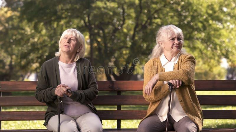 As senhoras maduras que sentam-se separadamente no banco no parque, amigos discutiram e discutiram fotografia de stock