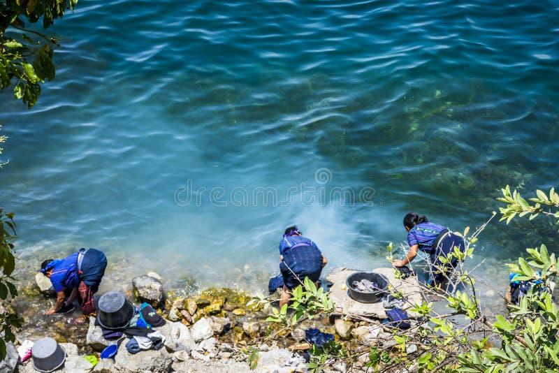 As senhoras nativas do Maya lavam a lavanderia na beira do lago, San Antonio Palopo, lago Atitlan, Guatemala imagens de stock